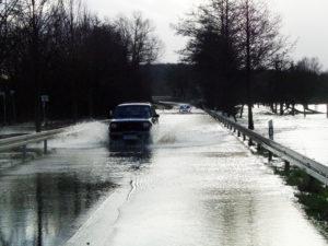 Überflutete Straße auf der ein Auto fährt