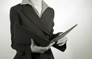 Frau in einem Anzug hält eine Handakte und liest daraus